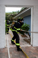 Firefighters running hose into house